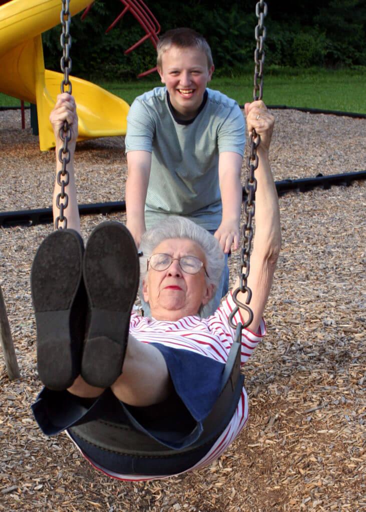 Young boy pushing gran on a swing